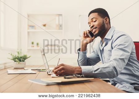 Satisfying call. Young businessman talking on mobile phone and taking notes in modern white office, copy space