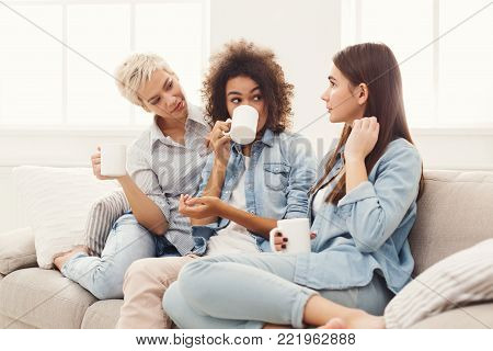 Diverse female friends at home. Three young women with coffee cups chatting on sofa, gossiping and sharing secrets, discussing life and relations. Friendship, trust and slumber party concept