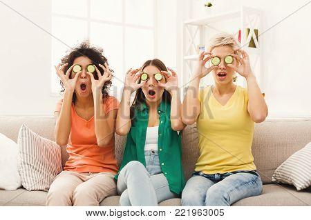 Three beautiful girls in colourful clothes laughing, having fun, covering eyes with cucumber pieces