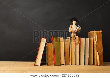 Educational background. Wooden marionette in graduation hat sitting on old books and reading against empty classroom blackboard for copy space. Back to school concept