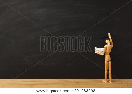 Educational background. Wooden marionette writing someting with chalk on clear blackboard with copy space for text. Back to school concept