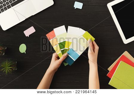 Woman's hands holding a palette of colors. Top view of human hands, laptop, notebook, palette of colors and digital tablet on a wooden table background. Designer, working process concept