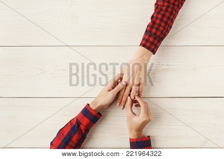 Boyfriend putting ring on girlfriend finger. Man propose to marry him. Happiness, relationships, love, engagement concept, copy space, top view