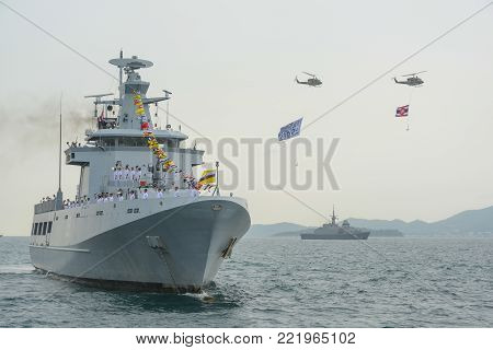 Pattaya, Thailand - November 20, 2017: Navy warships running on sea while helicopter with Thai Navy flag and IFR2017 flag flying above warships on the 50th anniversary ASEAN international fleet review 2017 in Pattaya, Thailand