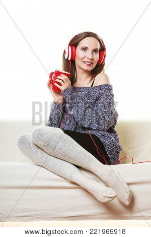 People leisure relax concept. Woman casual style red big headphones listening music mp3, sitting on couch at home relaxing drinking hot tea coffee