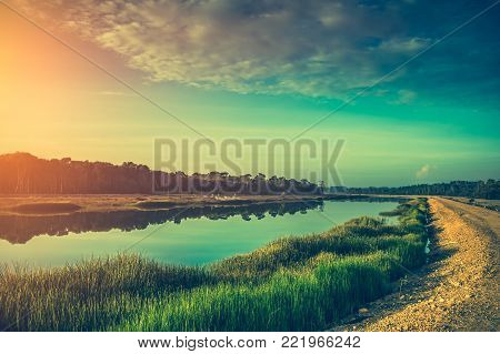 Beautiful landscape of emerald green sky with sunlight and along the riverside road. Serenity nature background. Outdoors on summer day. Cross process and vintage film filter effect. poster