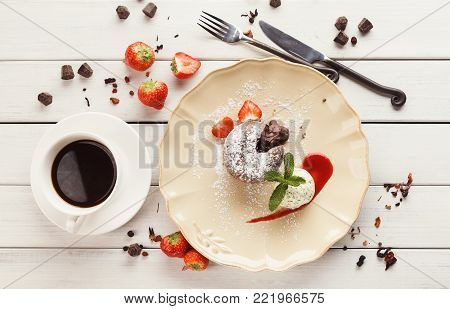 Chocolate lava cake served with vanilla ice cream and strawberry on classic porcelain plate, top view
