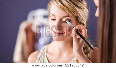 Artist doing professional make up of woman. poster