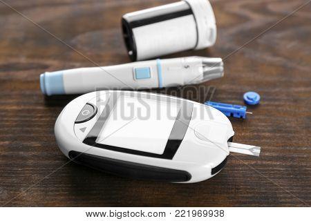 Digital glucometer and lancet pen on wooden background. Diabetes management
