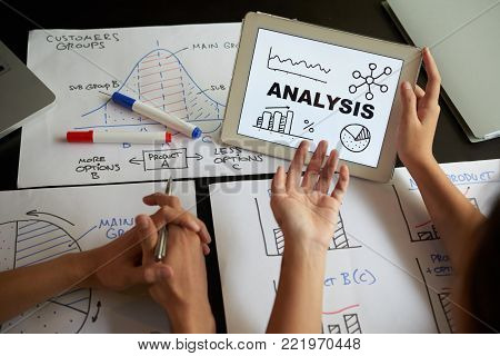 Various charts and graphs on table of business people whe are having meeting