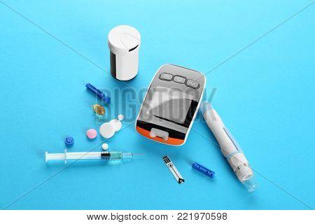 Digital glucometer, lancet pen, syringe and medicaments on color background. Diabetes management