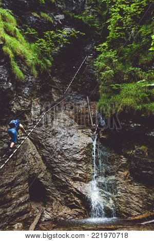 Hiker is climbing up to the rock in the Tatra Mountains in Slovakia. Outdoor extreme activity in the wild wood. Thrilling leisure rock climbing using metal ladder. Green tourism.
