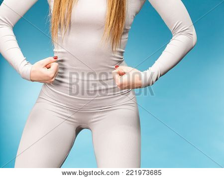 Fit woman wearing hot gray sports thermolinen underwear, closeup part of body, studio shot on blue. Long sleeves top and leggings.