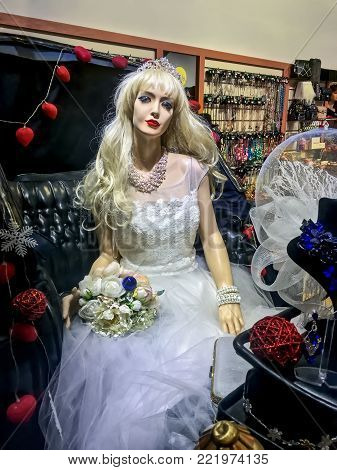 LVIV, UKRAINE - DECEMBER 18: Dummy of a young girl in a wedding dress sitting in a britzka in a shop window in the center of Lviv on December 18, 2017 in Lvov, Ukraine