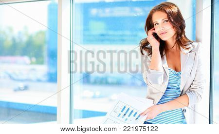 Portrait of young businesswoman talking on mobile phone on office hallway.