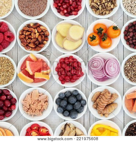 Healthy super food selection with fresh fruit, vegetables, fish, seeds, nuts, spice and herbs with foods high in omega 3 fatty acids, antioxidants, anthocyanins, fibre and vitamins.