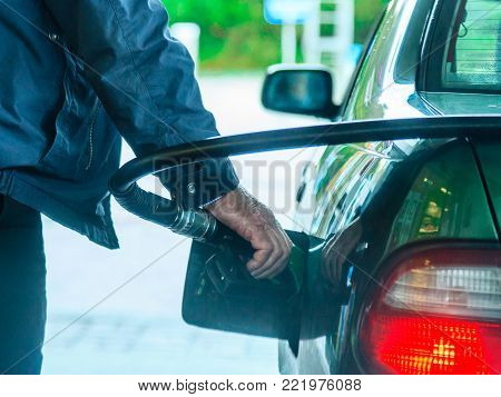 Male hand refilling the car with gas or petrol on filling station, holding a fuel pump outdoor