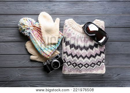 Warm clothes with ski goggles and photo camera on wooden background. Winter vacation concept