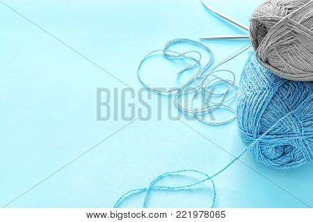 Woolen clews on color background
