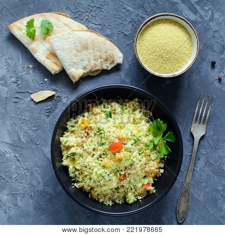 Tabbouleh salad and flatbread on concrete background. Lebanese, arabic cuisine. Healthy vegan cous cous salad in black bowl. Table top view, square crop