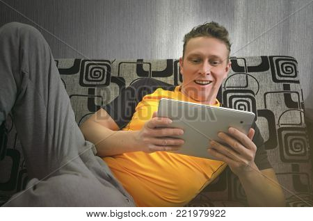 Happy smiling man is laying on a sofa, holds in hands a tablet computer and is watching a movie film. Idler man.
