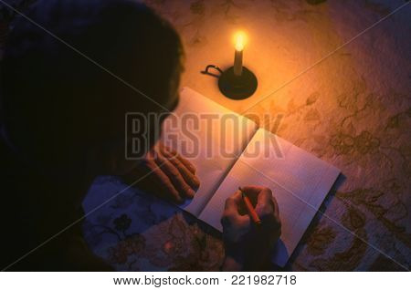 Man is studing and writes in a notebook by lies on the floor in the light of candle. Person writes a letter. Writer. Education background.