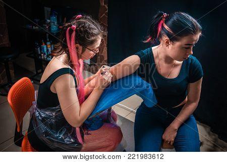 Master tattooist makes tattoo art tatoo salon.