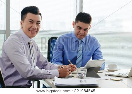 Cheerful Vietnamese businessman attending meeting in office