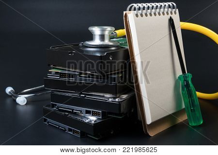 Hard disk drive, screwdriver, stethoscope and notebook for text on black background for protect data, repair, fixed, service and recovery concept. Computer hardware hard disk concept.