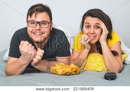 man with woman watchin TV in bed with snacks in front of them