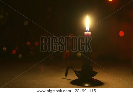 A burning candle in the darkness. Candle in the candle holder with copy space.