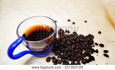soft focus of a cup of energetic drink infusion and coffee beans with a raw background. for detox and healthy concept