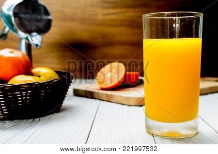 The Freshly Squeezed Orange juice on the white wood table and in front of sliced oranges in the wicker brown basket.