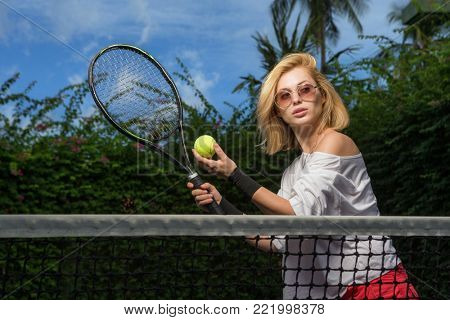 Woman hand holding tennis ball and racket in court. tennis ball on hand.