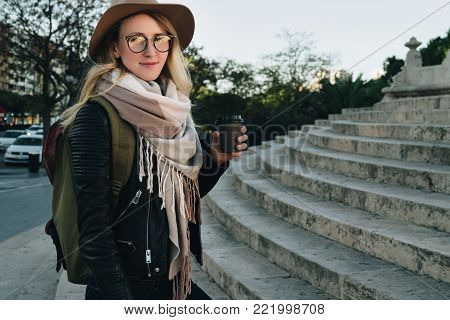 Sunny autumn day, backlight. Young attractive woman tourist in hat, eyeglasses and with backpack stands on city street, drinks coffee. Hipster girl walks, looks at sights. Vacation, adventure, trip.