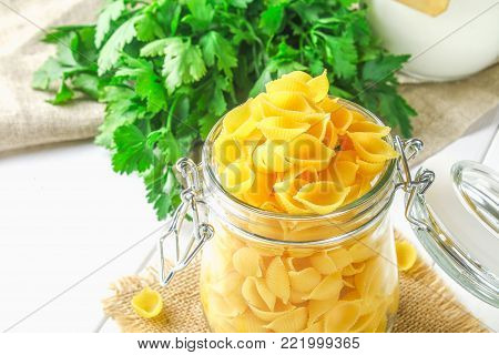 Culinary background with conchiglie pasta on wooden table. Pasta in the form of cockleshells in a glass jar with parsley