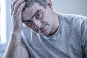 40s or 50s sad and worried man with grey hair sitting at home couch looking depressed and wasted in sadness face expression in depression and life problems concept poster