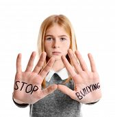 "Teenage girl with words ""Stop bullying"" on her hands against white background poster"