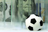 Close-up. Souvenir soccer ball with medical test tubes against the background of one hundred dollar bill. Concept money and sports, medicine and football, corruption and doping. Macro. poster