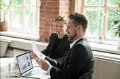 Two satisfied executives discussing company growth project success financial statistics with rising graphs on laptop screen, businessman holding document showing increasing stats to partner in office poster