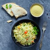 Tabbouleh salad and flatbread on concrete background. Lebanese, arabic cuisine. Healthy vegan cous cous salad in black bowl. Table top view, square crop poster
