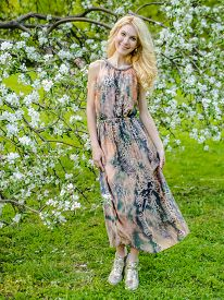 beautiful Russian girl blonde in a summer tight-fitting dress against the background of a blossoming apple tree