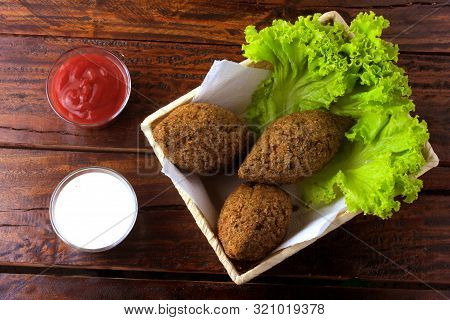 Fried Kibbeh With Tomato Sauce In A Basket, Over Rustic Wooden Table. Top View