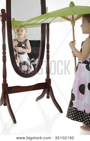 An adorable preschooler with a parasol, checking herself in the mirror.  Focus on her face in the mirror.  A trunk of dress-up clothes is behind her (seen only in the mirror).  On a white background.