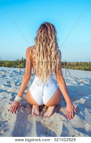 Beautiful And Slender Figure Of A Girl In A White Bathing Suit, View From The Back, Long Hair, Tanne