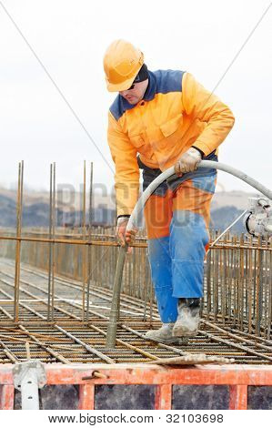 builder worker with vibrator machine compacting poured concrete into reinforcement formwork