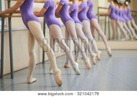 Ballerinas In Purple Suits At Ballet Barre. Ballet Barre Workout Moves. Improving Tendus In Ballet.