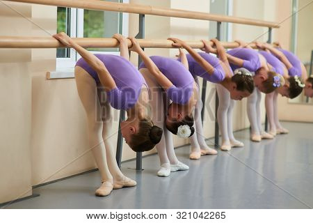 Young Ballerinas Performing Flexibility Exercises. Group Of Young Ballet Dancers Bent Down At Ballet
