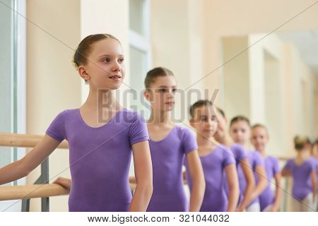 Young Ballet Performers At Ballet School. Group Of Cute Ballet Girls Standing Near Ballet Barre At D