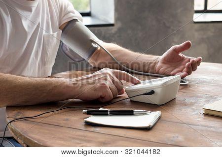 Man Using Home Blood Pressure Machine To Check His Vital Statistics.